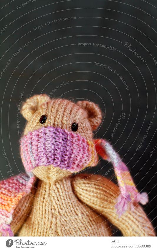 Iff fkann nikfs mea fsagen, kleiner, gestrickter Teddy mit buntem Schal um den Mund als Mundschutz, gegen Ansteckung mit Viren, Corona und Grippe, schaut traurig und ängstlich, vor einer schwarzen Tafel im Hintergrund..