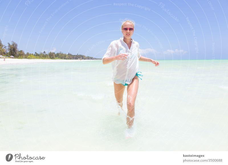 Junge aktive Frau, die Spaß am Laufen und Plantschen in Muschelseewasser hat. Strand MEER platschen Sommer Schönheit Mädchen im Freien schlank reisen tropisch