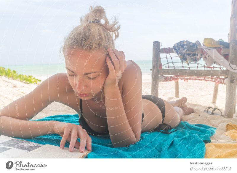 Hübsches Mädchen liegt am Strand im Badeanzug und liest ein Buch Sand MEER Sommer Bikini Handtuch Urlaub Frau schön sexy Sonnenbad Bräune reisen Kaukasier