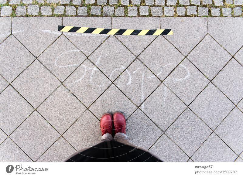 Gelb-schwarzes Absperrband und das Wort Stopp auf dem Gehweg fordern eine weibliche Person zum Abstandhalten in Zeiten von Corona auf gelb-schwarz Halt