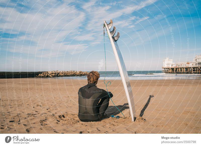 Surfer, der am Sandstrand und neben dem Surfbrett sitzt. Mann Brandung Wasser Sport Surfen MEER Meer im Freien sportlich Küstenlinie Wellen Hintergrund