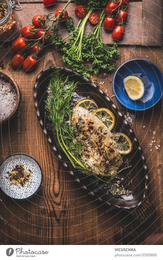 Gebackenes gebratenes Fischfilet in Backform mit Dill und Zitrone auf Holzuntergrund, Ansicht von oben. Konzept der Hausmannskost. Meeresfrüchte, Low Carb und Diätnahrung