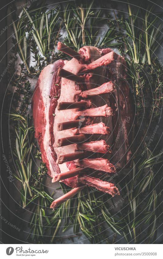 Nahaufnahme von rohen Lammkarrees. Dunkler rustikaler Küchentisch mit Kräutern und Gewürzen. Ansicht von oben. Rohes Fleisch. Herstellung von Lammkronenbraten