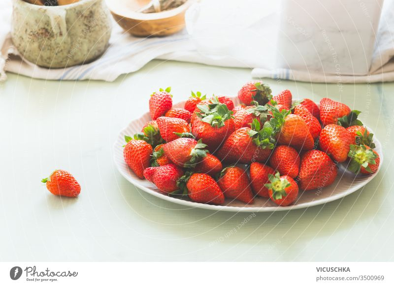 Bio-Gartenerdbeeren in weißer Platte auf hellem Küchentisch . Gesunde Nahrung der Saison. Haufen reifer Beeren organisch Teller Licht Tisch Gesundheit