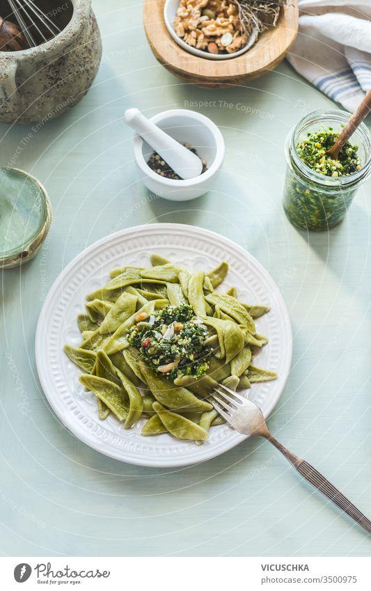 Draufsicht auf einen gesunden Mittagstisch mit grünen Nudeln oder Pasta und Pesto auf hellem Hintergrund. Ansicht von oben. Gesundes vegetarisches Essen