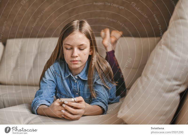 Ein hübsches Mädchen im Teenageralter kommuniziert während der Quarantäne per Bote mit ihren Freunden. Selbstisolation, Kommunikation, soziale Distanz während der Quarantäne