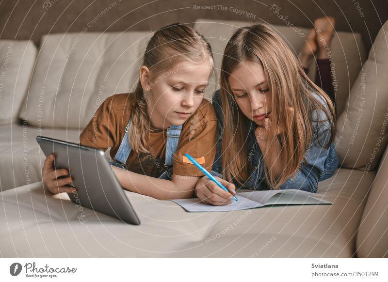 Zwei schöne Schwestern machen während der Quarantäne ihre Hausaufgaben. Kinder verwenden zum Lernen Geräte. Bildung, Fernunterricht, Heimunterricht während der Quarantäne