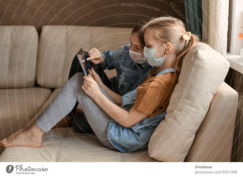 Zwei süße Mädchen mit medizinischen Masken sitzen mit einer Tablette auf dem Sofa. Schulmädchen machen ihre Hausaufgaben. Fernunterricht während der COVID-19-Quarantäne.