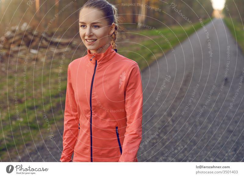 Lächelnde, sportlich-sportliche junge Frau, die auf einer geteerten Bahn durch Wälder, die vom warmen Schein der Sonne beleuchtet werden, in einem gesunden, aktiven Lebensstil trainiert
