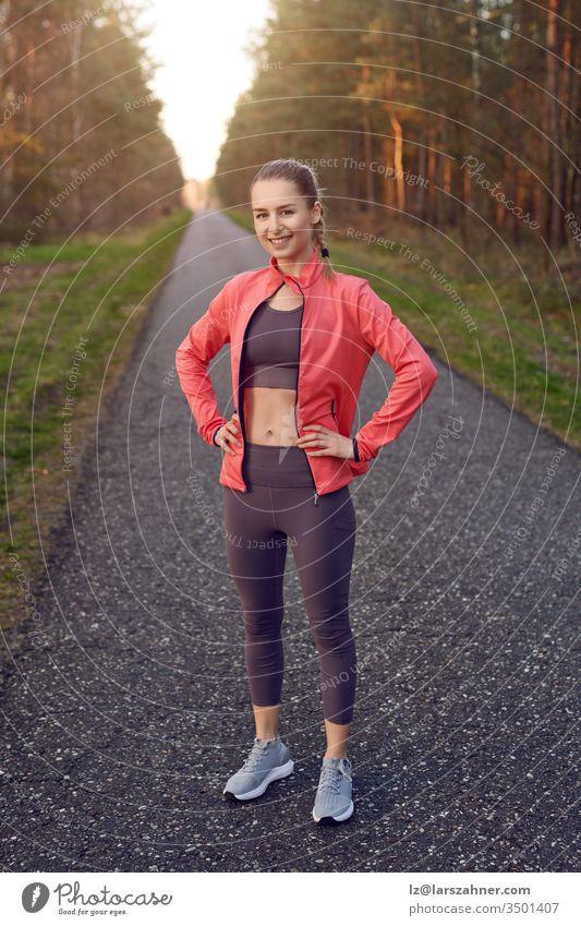 Ganzflächiges Frontporträt eines sportlichen jungen Mädchens in Trainingskleidung mit grauer Hose und roter Jacke, das nach dem Joggen mit den Händen auf den Hüften steht und sich ausruht, in die Kamera schaut und lächelt