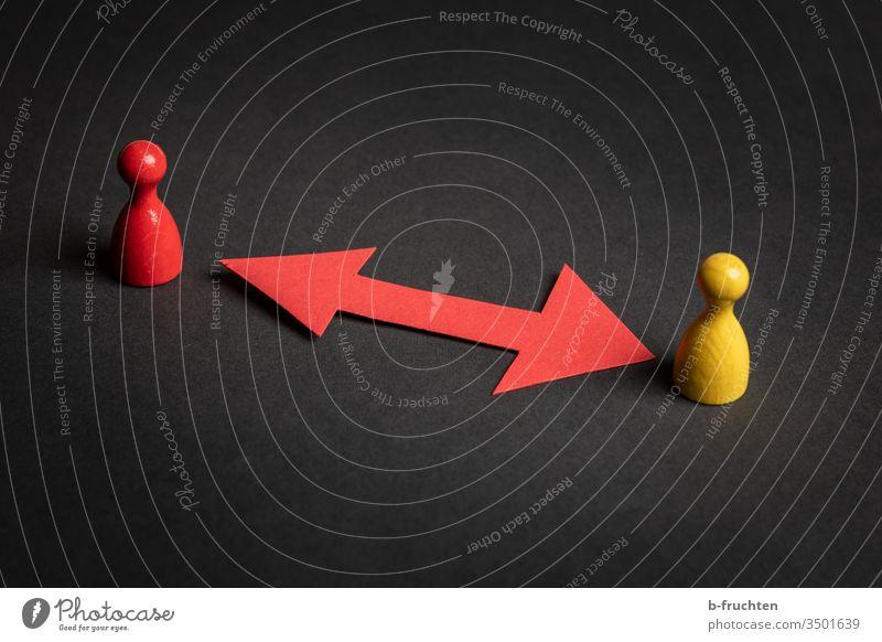 Zwei Spielfiguren mit einem roten Richtungspfeil aus Papier, schwarzer Hintergrund. Pfeil sicherheit abstand spielfigur gelb schützen pfeile papier zwei paar