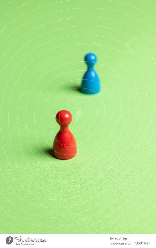Zwei Spielfiguren mit Abstand, Social Distance. rot blau grün abstand Nahaufnahme Farbfoto Spielzeug Spielen social distancing social distance virus