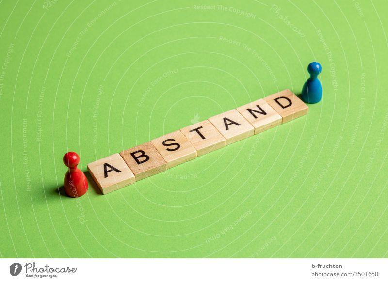 Abstand halten. Scrabblesteine zwischen zwei Spielfiguren Buchstaben wort Social Distance social distancing grün blau Pandemie Infektionsgefahr Corona-Virus