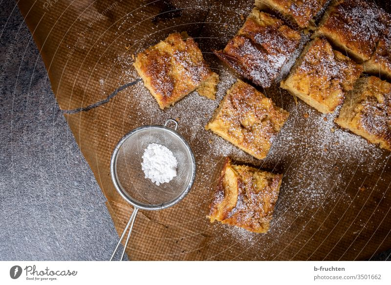 Apfelkuchen auf Backpapier Kuchen Stücke Sieb Puderzucker süß Lebensmittel lecker Ernährung Zucker Dessert Frucht Vegetarische Ernährung backen Backwaren