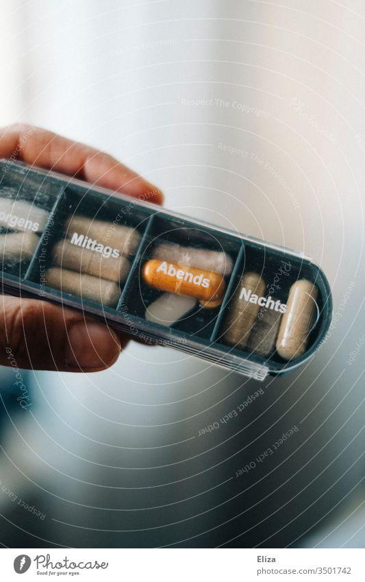 Eine Person hält eine Medikamentenbox, in die verschiedene Tabletten und Pillen für die unterschiedlichen Tagseszeiten sortiert sind, in der Hand