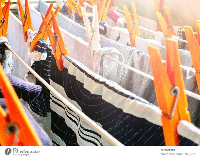 eine Gruppe von orangefarbenen Wäscheklammern auf einem Trockengestell zum Trocknen der Wäsche. Wäsche, die zum Trocknen in einem Haus aufgehängt wurde. Hausarbeit und Hygiene.