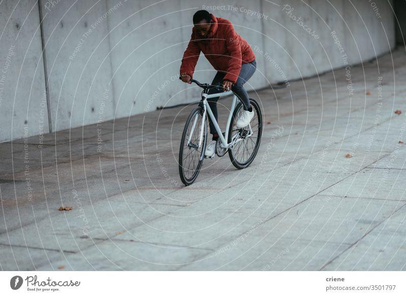 Fahrradfahrende Frau in städtischer Umgebung Radfahrer Afroamerikaner in Bewegung Lifestyle aktiv urban Verkehr jung umweltfreundlich Großstadt Stadtleben