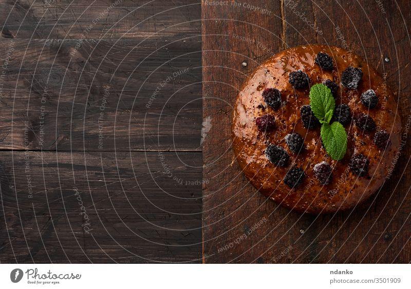 gebackener runder Biskuitkuchen mit Nüssen und Beeren belegt, brauner Holztisch schwarz Brot Kuchen Nahaufnahme Koch Essen zubereiten Küche dunkel lecker
