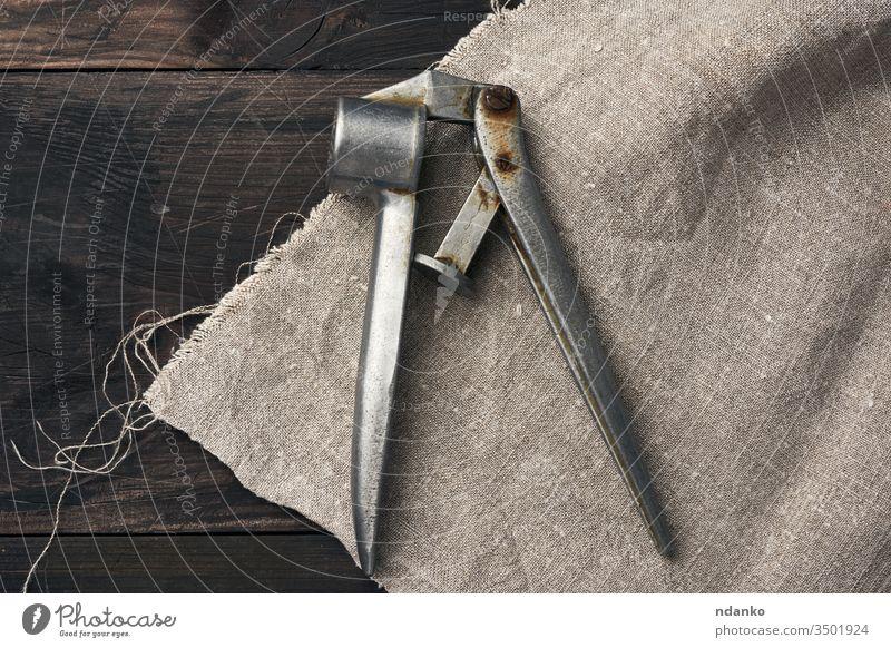 alte Metallpresse für Knoblauch und andere Gewürze auf einem braunen Holztisch Brecher Presse Hintergrund Küche Lebensmittel rostfrei Werkzeug Stahl metallisch