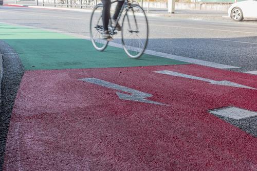 Fahrradweg mit einem Übergang von Grün zu Rot mit einem Radfahrer Aktion aktiv Aktivität Pfeil Asphalt Berlin Biker Radfahren Großstadt Zyklus Regie Übung