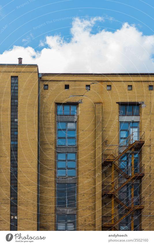 Altes Industriegebäude von außen mit verrosteter Treppe Verlassen antik Appartement architektonisch Architektur Hintergrund Blauer Himmel Baustein Gebäude