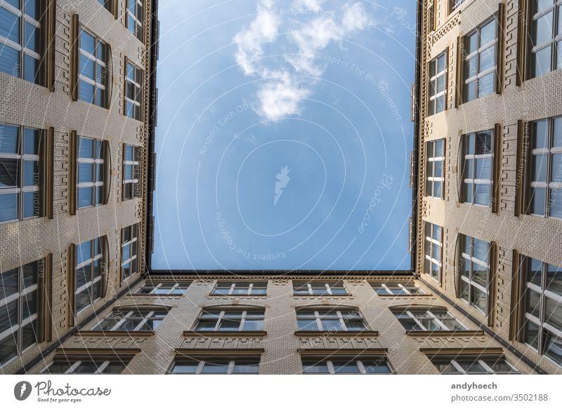 Ein Blick auf eine weiße Wolke von einem Innenhof Appartement Appartements Architektur schön blau Blauer Himmel Baustein Gebäude Großstadt Wolken Konstruktion