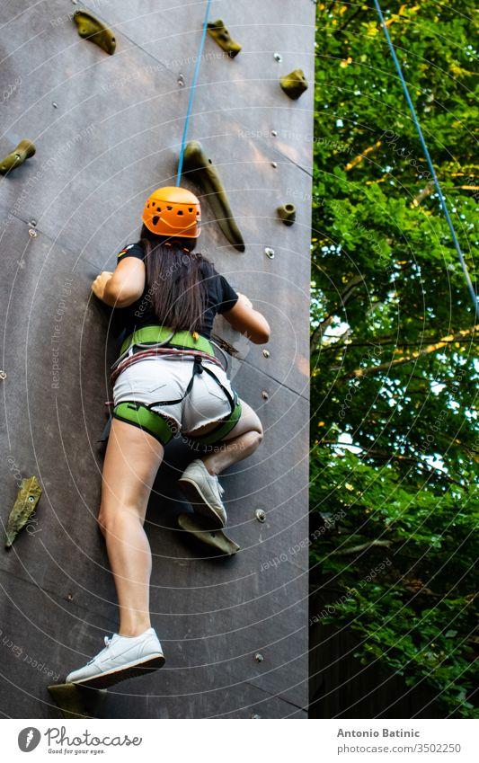 Frau in Shorts und schwarzem Hemd mit Sicherheitsausrüstung beim Klettern an einer künstlichen Kletterwand. aktiv Aktivität Erwachsener Abenteuer allein schön