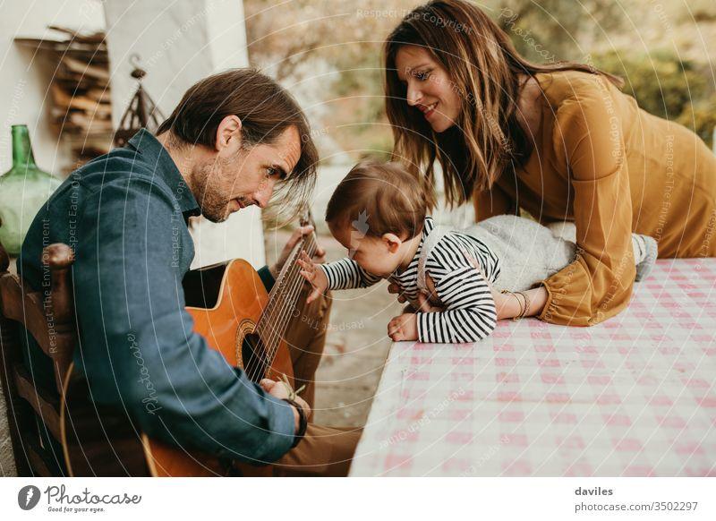 Ein einjähriges Baby, das die Gitarre seines Vaters berührt, während es auf dem heimischen Hof spielt. Die Mutter hält das Baby. klein Windstille Garten lässig