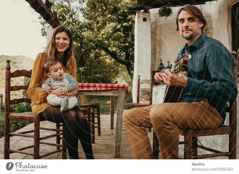 Schönes Paar mit ihrem Kleinkind, das gerne auf dem Hof auf dem Land sitzt. Mann spielt Gitarre. Frau hält das Baby. Sie schauen in die Kamera. klein Windstille
