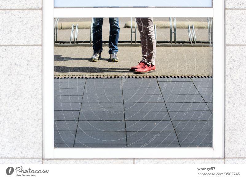 4 Füße auf Entdeckungsreise spiegeln sich in einer Fensterscheibe Stadt Erkundung rumstehen Gehweg Spiegelung Reflexionen Außenaufnahme Tag Farbfoto