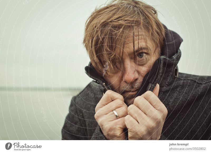 Huschi Haarsträhne Mann Porträt Mensch Blick kalt frieren Frost Winter See Gewässer verwegen Außenaufnahme Mantel Blick in die Kamera bad hair day Strubbelig