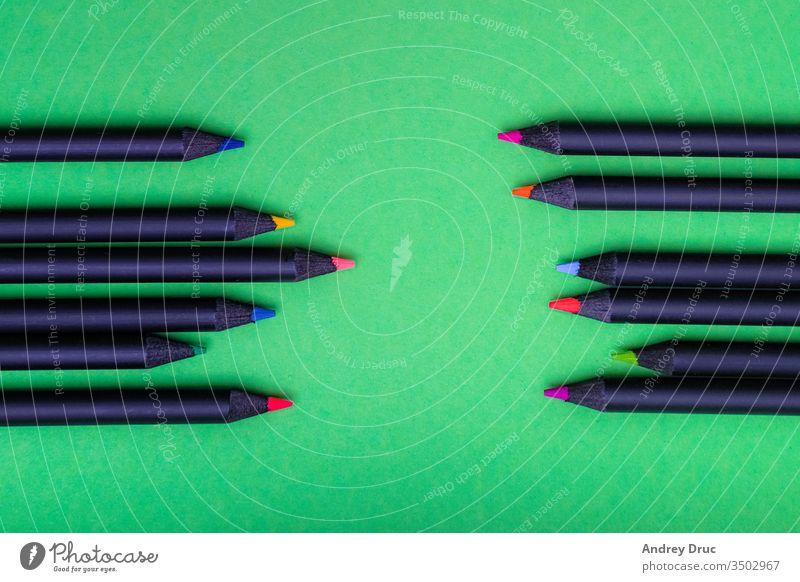 Farbstifte in verschiedenen Farben auf grünem Hintergrund abstrakt Kunst Aufmerksamkeit schwarz blau Haufen Business schließen Hochschule farbig Buntstifte
