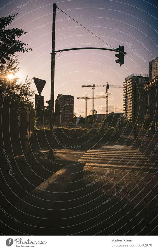 Im Gegenlicht des Sonnenuntergangs stehen Baukräne, Verkehrsschilder und eine Ampel am Zebrastreifen. Straßenverkehr Himmel Golden Hour goldene stunde analog
