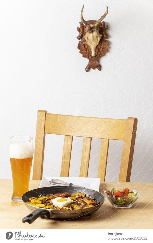 Tiroler Kartoffelgröstl mit Zwiebeln Gröstl Pfanne gebraten Herz Liebe Übersicht Speck Nahaufnahme Tisch Stuhl Geweih groestl Essen Fleisch Hintergrund Ei