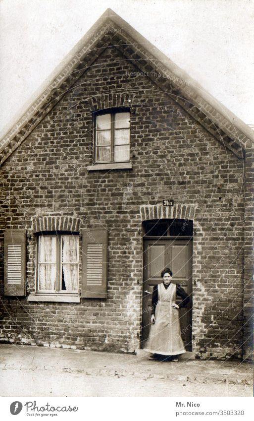 Oma ihr Häusschen Nachkriegszeit Vergangenheit Nostalgie Erinnerung analog Eingangstür Haus Großmutter Leben alt Tür Kittel Schürze stehen Schwarzweißfoto