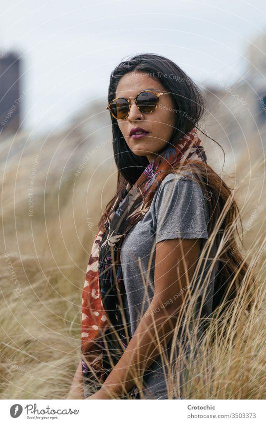 Bildnis einer brünetten Frau mit Sonnenbrille, die in einem Weizenfeld einen Schal am Hals trägt Schönheit arabisch Porträt Feld wild drehen. Gesicht
