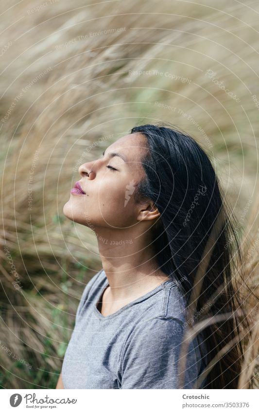 Porträt einer jungen brünetten Frau mit geschlossenen Augen beim Meditieren vertikal Ausdruck Gesicht Profil träumen Erhöhung Sonnenlicht Feld Natur bequem