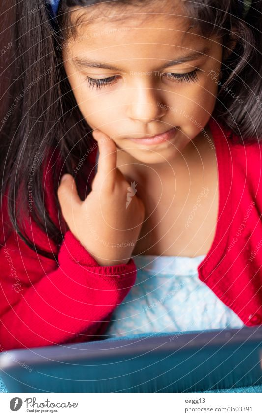 Kleines Mädchen sitzt und spielt zu Hause mit ihrem Tablett Lebensalter Kinder bequem Mitteilungen verbunden Liege Herunterladen lehrreich elearning kurzweilig