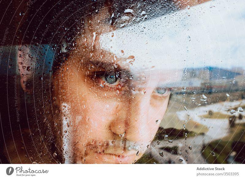 Depressiver Mann schaut durchs Fenster traurig Depression Isolation Coronavirus heimwärts verzweifelt einsam unglücklich jung männlich nass Regen Melancholie