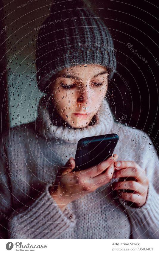Junge Frau mit Smartphone am Fenster stehend heimwärts benutzend einsam traurig Selbstisolierung Isolation Browsen Apparatur Coronavirus COVID Quarantäne jung