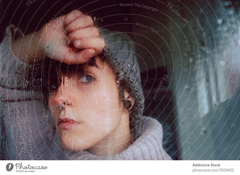 Melancholische junge Frau schaut durchs Fenster traurig Depression Isolation Coronavirus heimwärts verzweifelt einsam unglücklich männlich nass Regen