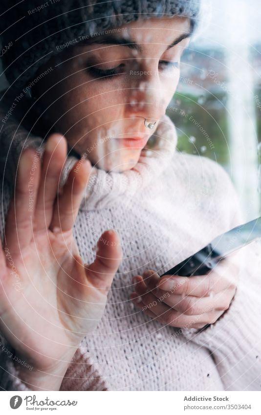 Junge Frau mit Smartphone am Fenster stehend heimwärts benutzend einsam traurig Selbstisolierung Isolation Browsen Apparatur Coronavirus covid-19 Quarantäne