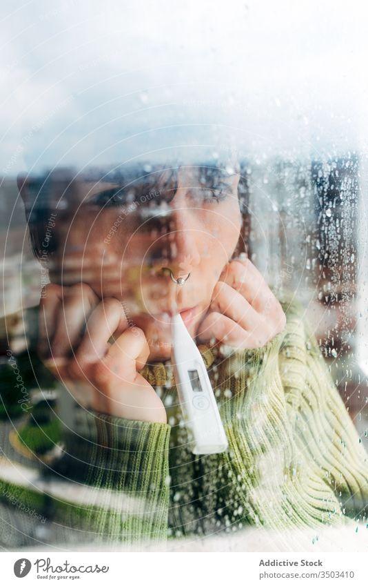 Kranke Frau, die zu Hause in Fensternähe die Körpertemperatur kontrolliert krank Thermometer heimwärts Coronavirus Isolation Temperatur Fieber Kopfschmerzen