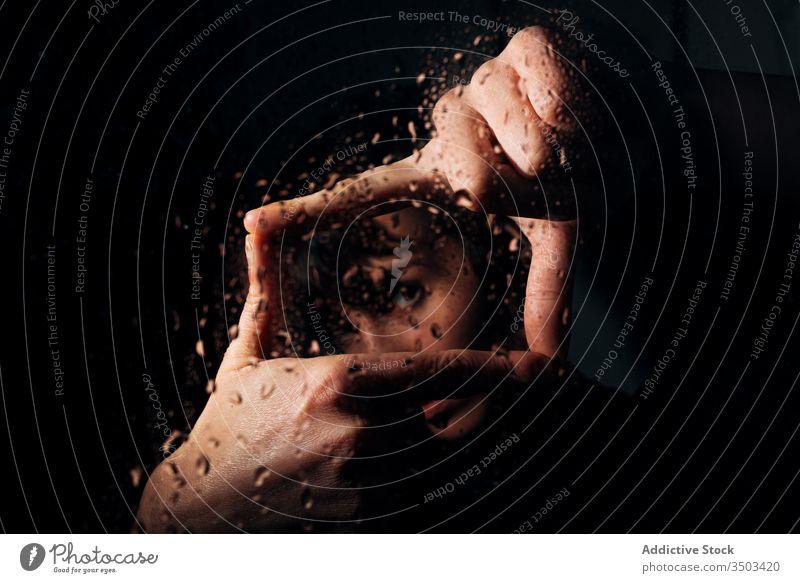 Junge Frau schaut durch Fenster in dunklen Raum traurig Depression Isolation Coronavirus dunkel heimwärts Rahmen Hand gestikulieren einsam unglücklich jung nass