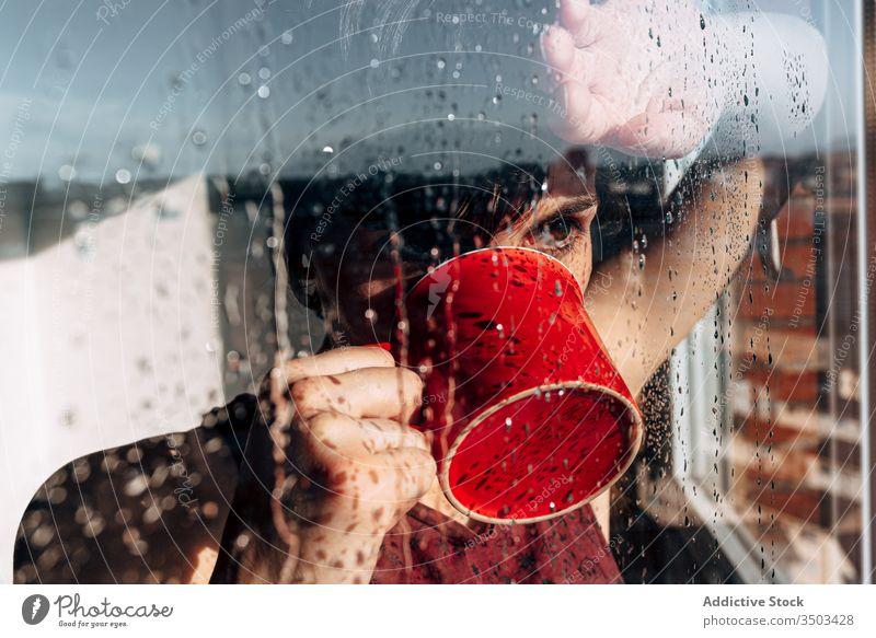 Nachdenkliche Frau trinkt Kaffee am Fenster traurig Depression trinken Selbstisolierung heimwärts unglücklich einsam COVID19 Melancholie jung nass Regen