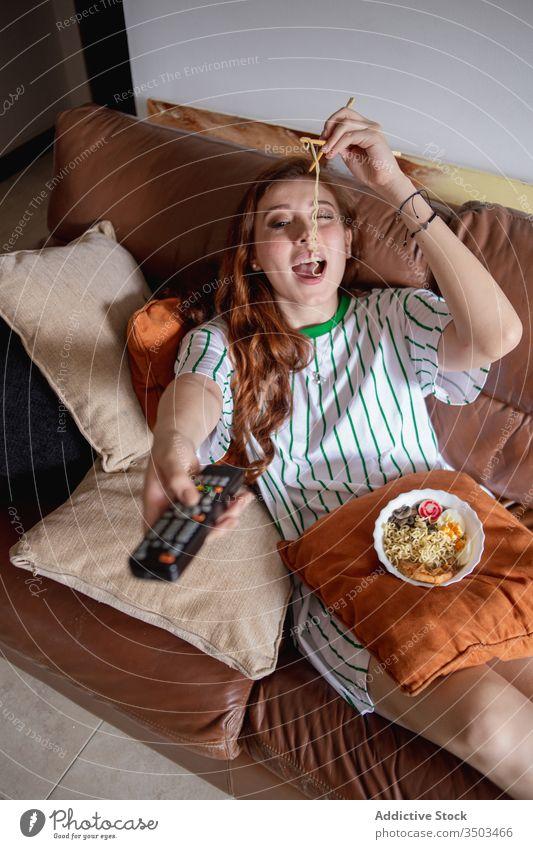 Junge Frau isst Nudeln und sieht fern Ramen essen zuschauen FERNSEHER heimwärts Mittagessen jung ruhen Japanisch Sofa Filmmaterial Wandel & Veränderung Kanal