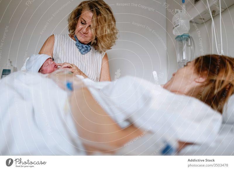 Frau besucht Tochter mit Neugeborenem im Krankenhaus neugeboren Baby Mutter Großmutter Frauen Pflege Bett besuchen Gruß Klinik Glück neonatal Kind Medizin
