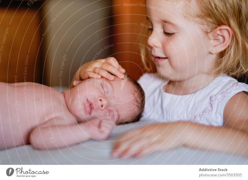 Glückliches kleines Mädchen streichelt mit Liebe Neugeborenes schläft zu Hause in weichem Bett neugeboren Streicheln Kind Schwester Säugling Windstille
