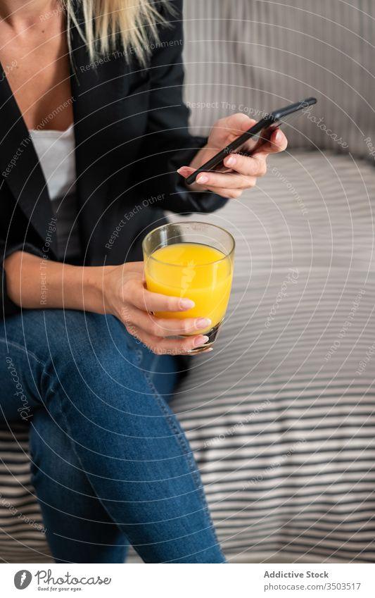 Anonyme Frau trinkt Saft und benutzt Smartphone auf dem Sofa benutzend heimwärts Handy trinken ruhen soziale Netzwerke räkeln Gesundheit sitzen frisch orange
