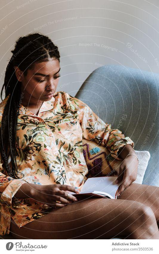 Ethnische Frau mit zu Hause ruhendem Buch heimwärts lesen Afrikanisch Amerikaner schwarz lässig Stuhl brünett Windstille Sitzen jung gemütlich ethnisch Freizeit
